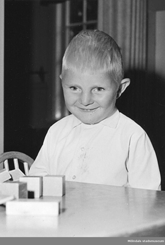 En pojke som sitter vid ett bord med byggklossar. Holtermanska daghemmet 1953.