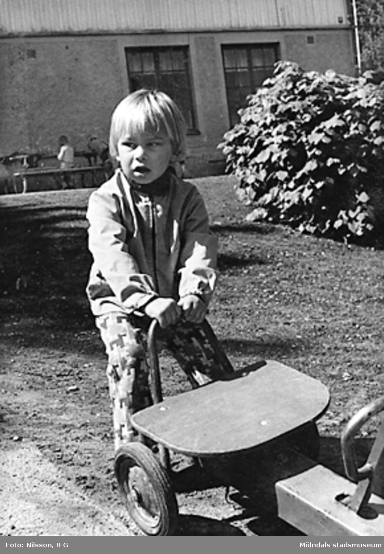 Ett barn håller i en trampbil. Holtermanska daghemmet juni 1973.