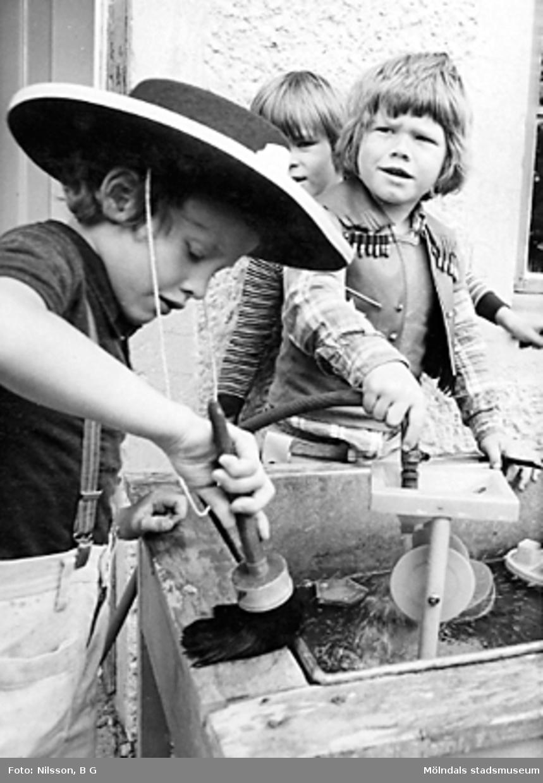 Tre barn som leker med verktyg utomhus. Holtermanska daghemmet juni 1974.