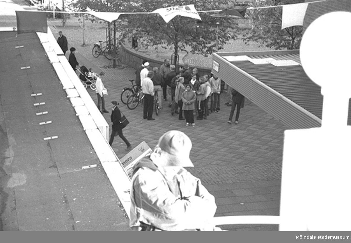 Människor samlade vid Brogatan/Mölndals torg. Främst i bild ses en ung man som står på parkeringsdäcket. Mölndalsbro i dag - ett skolpedagogiskt dokumentationsprojekt på Mölndals museum under oktober 1996. 1996_1024-1041 är gjorda av högstadieelever från Kvarnbyskolan 9C, grupp 1. Se även 1996_0913-0940, gruppbilder på klasserna 1996_1382-1405 samt bilder från den färdiga utställningen 1996_1358-1381.