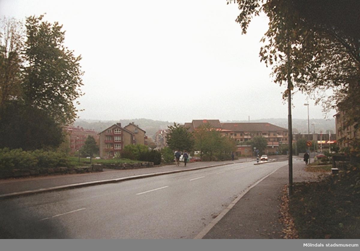 Vy österut mot Bergmansgatan sett från Frölundagatan. Till vänster skymtar kyrkans plantering. Mölndalsbro i dag - ett skolpedagogiskt dokumentationsprojekt på Mölndals museum under oktober 1996. 1996_1153-1171 är gjorda av högstadieelever från Kvarnbyskolan 9D, grupp 2. Se även 1996_0913-0940.