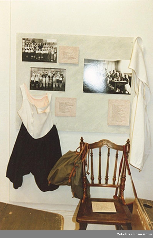 """Utställningen """"Lära för livet"""" 12 mars 1988 - 19 mars 1989 på Mölndals museum. Tre foton, texter, en handduk samt en vit tröja och svarta shorts sitter uppsatta på en vägg. Framför detta står en brun stol."""