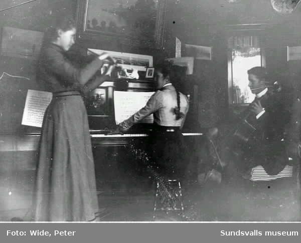 Familjen Wide musicerar (fiol, piano och cello)
