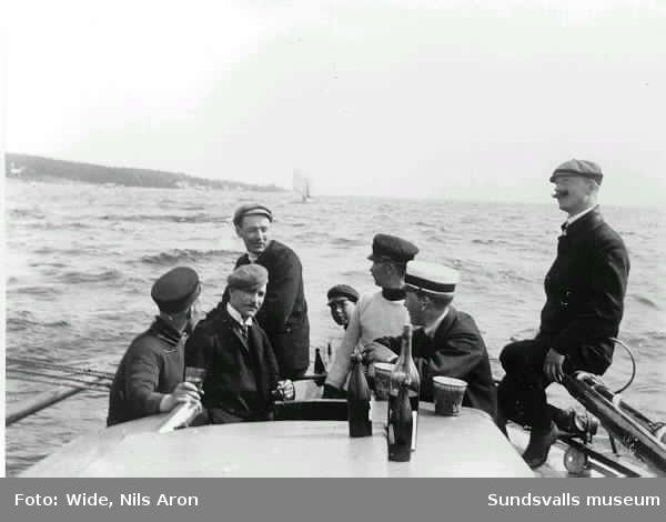 Okända sundsvallsbor på segeltur. Nils Aron Wide seglade då och då med vänner och fotograferade då med sin fars, Peter Wides, kamera. Troligen Alnö i bakgrunden.