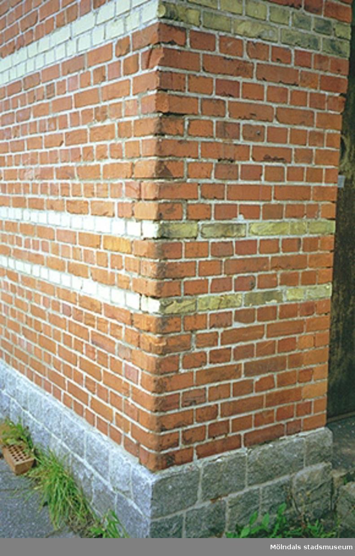 Man ser ett hörn av en industribyggnad, byggd av rödtegel, Göteborgsvägen 52, november 1994.