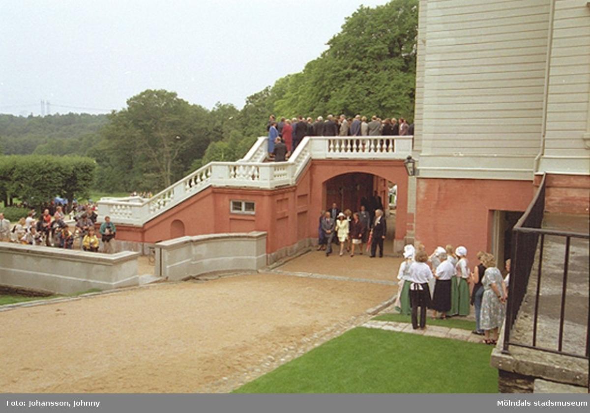 Besökare till vänster och kommunanställda på terrassen tittar på när kungaparet är på besök och promenerar under Gunnebo slottsterrass, 1997-08-27. Till höger ses slottets egen personal.