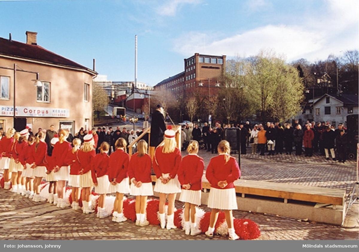 Gamla torget i Mölndal den 22:a november 2001. Folk lyssnar till tal som hålls av Lars Gahrn och Mölndals paradorkester underhåller.Invigning efter omläggning och stenläggning av torget. I bakgrunden ses den röda höga byggnaden Stora Götafors.