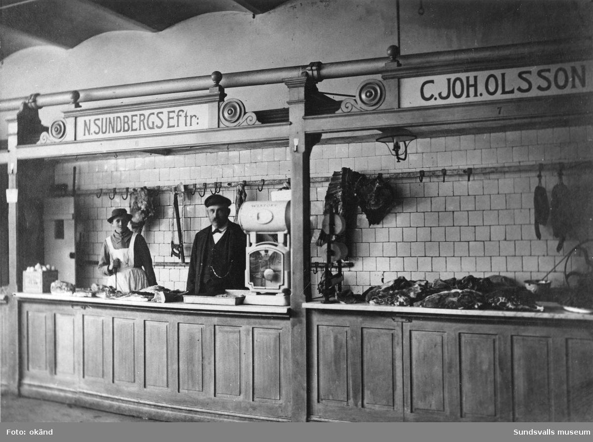 Köttbutik i Saluhallen i Holmströmska huset 1913. Carl Johan Olsson (45 år) med hustrun Olga (34 år). N. Sundbergs efterträdare. Paret var bosatt på Byggmästaregatan, Södermalm.