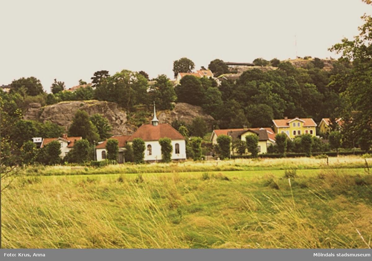 Missionskyrkan med bostäder och ängar i förgrunden. Översikt över stadsdelen Forsåker.
