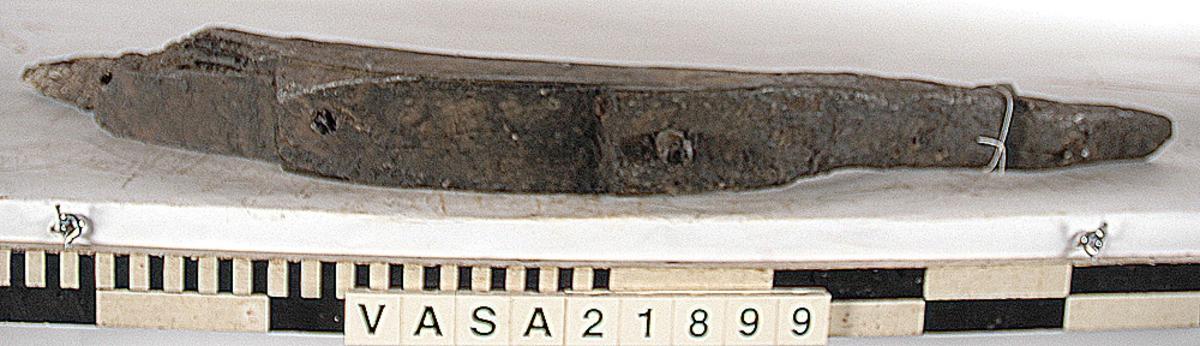 Spant/bottenstock till mindre båt. Toppänden är mycket välbevarad. Nedre änden är avbruten vid första våghålet. Tre hela dymlingshål samt ett trasigt. Tydliga verktygsspår. Ytan är delvis välbevarad.