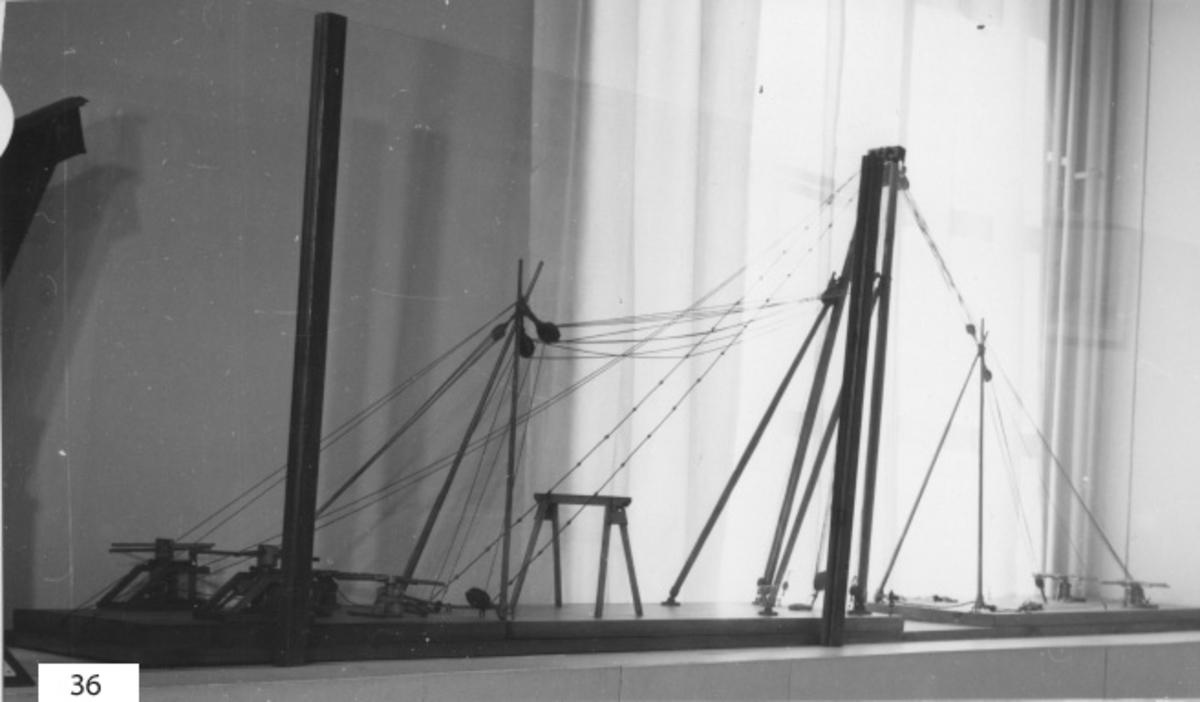 Mastkran modell utvisande anordningarna för uppresandet av mastkranen å nya varvet i K-na år 1874. Modellen består av masstkran med dubbla stag och hissgina, 8 st dubbla hjälpspiror, 6 st spel med bommar, 8 st taljor och 1 st block, allt av trä, fernissat.