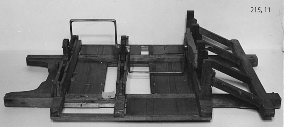 Modell av en aktersläde för hopslagning av dukter till en tross. För att få ut mer kraft, och därmed möjlighet att slå grövre trossar, har släden konstruerats med två metallvevar. Vevarna är löstagbara. Släden rullar på fyra hjul Modellen är av trä och obehandlad.  Tolkning: En konstruktionsmodell. Modellen är en av flera som ingår i Chapmans projekt för att förbättra repslageriet. Konstruktören Fredric Uhrlin utförde på uppdrag av af Chapman 1798 ett flertal modeller för nya repslageriinrättningen. Motsvarar troligen beskrivningen i modellkammarens inventarium år 1804 och 1834: Nya repslagare Inrättningen med tillbehör.    Nya Repslageriinrättningen med tillbehör. Modell av trä, omålad och bestående av 5 olika delar.