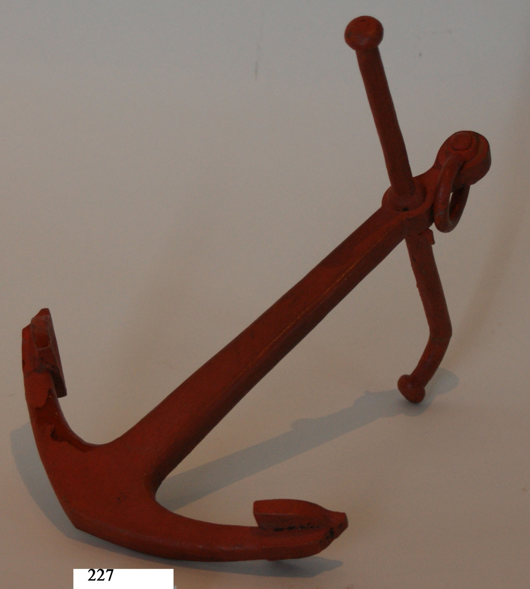 Skeppsankare, modell av trä, röringen av järn, rödmålad. Troligen från 1700-talet.