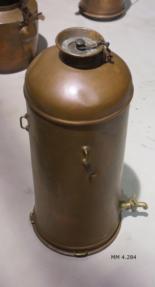 """Cistern, av koppar, för olja. Cylindrisk. Försedd med avtappningskran och 4 st rekt. upphängningsanordningar av mässing. Märkning: """"A.F.Hübenette No 280 Stockholm""""."""