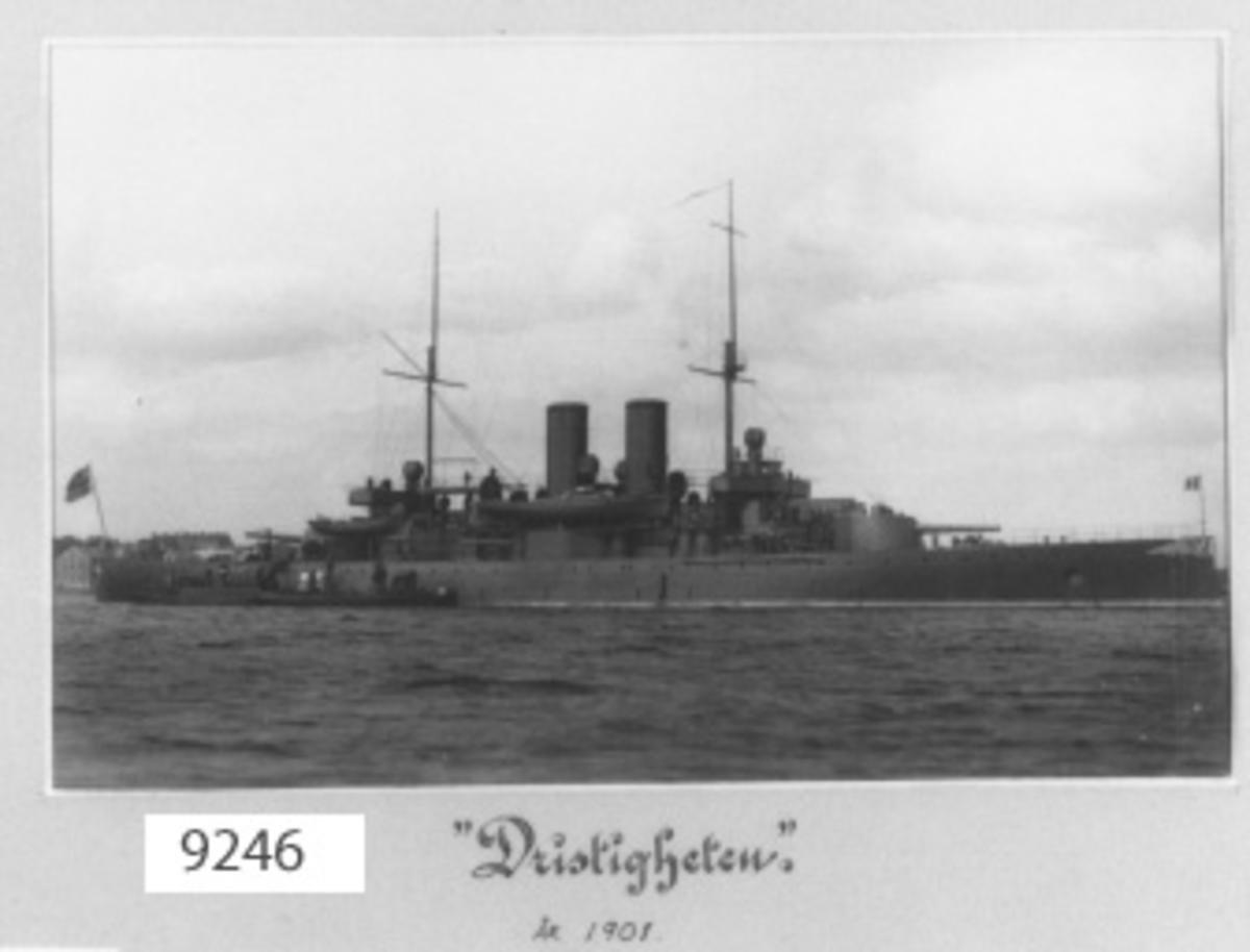 Fotografi inom ram av papp, ljusgrå. Visar pansarbåten Dristigheten till ankars på Karlskrona redd år 1901. Fartyget byggt år 1900 vid Lindholmens varv, Göteborg.