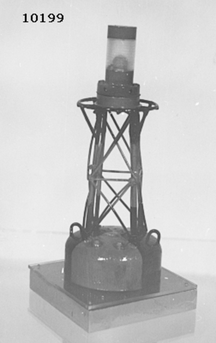 Modell av lysboj. Består nederst av en cylinder av trä med stativ av järntråd. I toppen lamphållare med el-lampa, skyddad av ett cylindriskt glas. Den cylindriska nedre delen har två röda och två svarta sektorer. Stativet är svart och rött. Bojen är monterad p en träplatta, botten och sidorna är ljusgrå, översidan är blå och täckt av ett plexiglas.