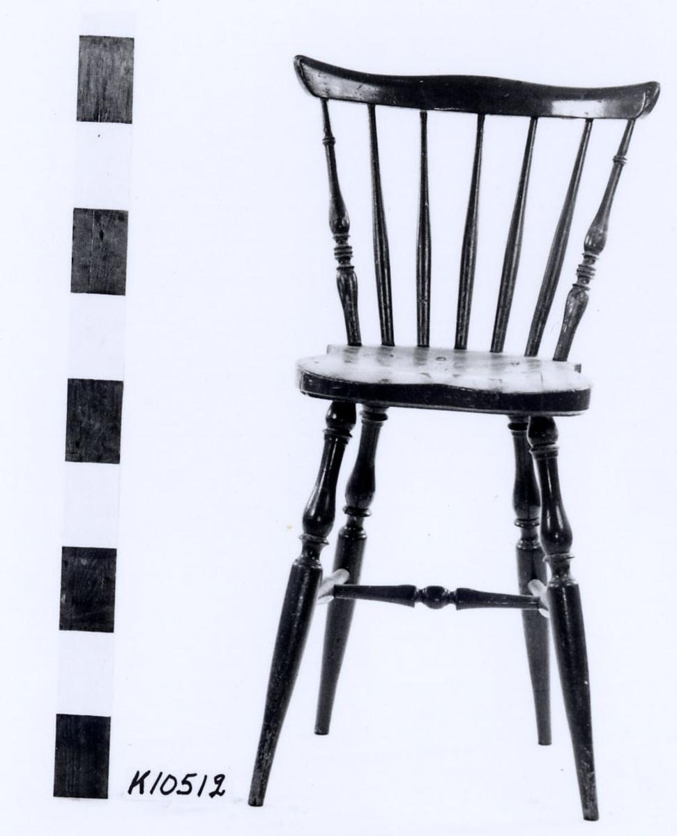 """Pinnstol av björk, grönmålad. Svarvade ben sammanhållna av tre slåar. Rygg av sju spjälor fastsatta i sits och överstycke. Märkning på sitsens undersida i svart färg: """"auf. Tillverkad vid Gemla fabriks AB Diö""""."""