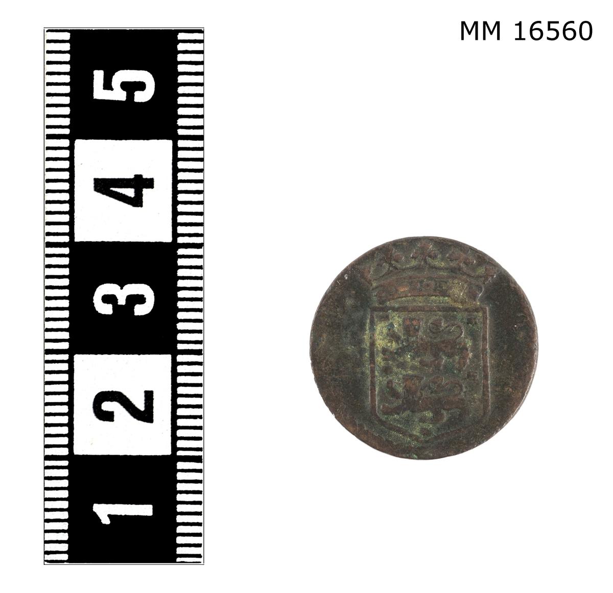"""Mynt, 1 dmt, ostindiska komp. Ena sidan: upphöjd relief: """"Voc 1748"""". Andra sidan: upphöjd relief: krönt vapensköld med två lejon. Innanför myntets kant har funnits någon form av upphöjd ornamentering."""