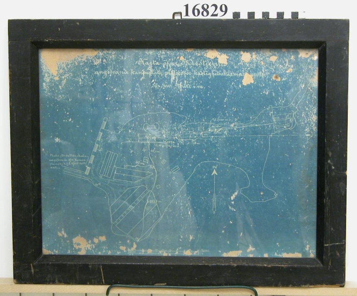 """Blåkopia inom glas och ram, som visar karta över Söderstjärna med rubrik """"Karta öfver Söderstjärna angifande kanonplan, plats för hastighetsskälmar med mera SK 1/1000 mått i m"""". Bildens bottenfärg är blå, alla linjer vita. Mått utskrivna på kartan i meter. Ram av svartmålat trä, 42 mm bred, baksida papp med blyertstext """"1 st sk upp den 11/12........."""" (oläsligt)."""