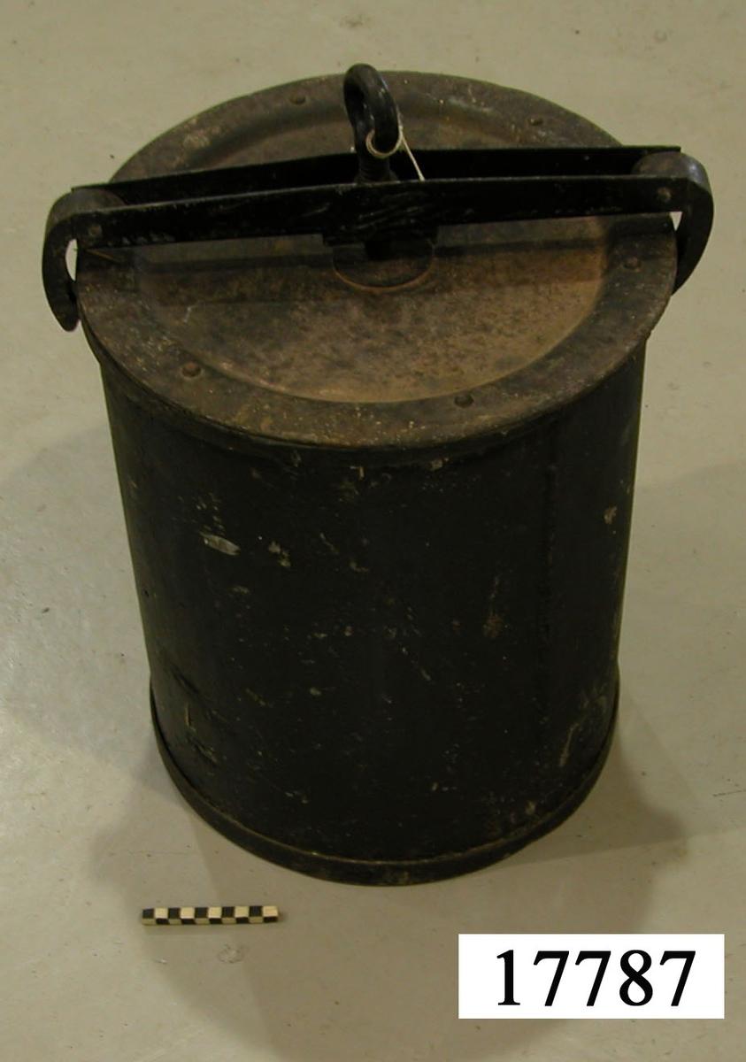 Latrintunna av svartmålad järnplåt, cylinderformad. Kanterna förstärkta med fastnitade järnband. Försedd med plant lock samt bygel som spännes runt tunnan och skruvas fast mot locket med en skruv.