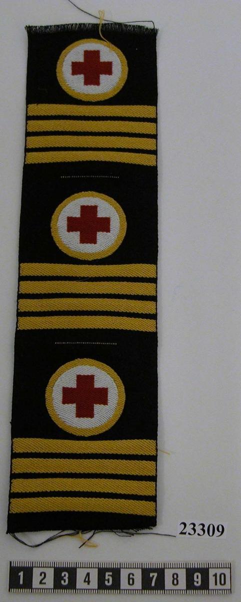 Yrkesemblem och gradbeteckning (tre stycken) för stamanställd högbåtsman, sjukvårdare. Ett vävt rött kors på vävd, vit, rund bakgrund med en vävd gul cirkel runt det vita området samt fyra vävda gula streck. Symbolen vävd på svart tyglapp.