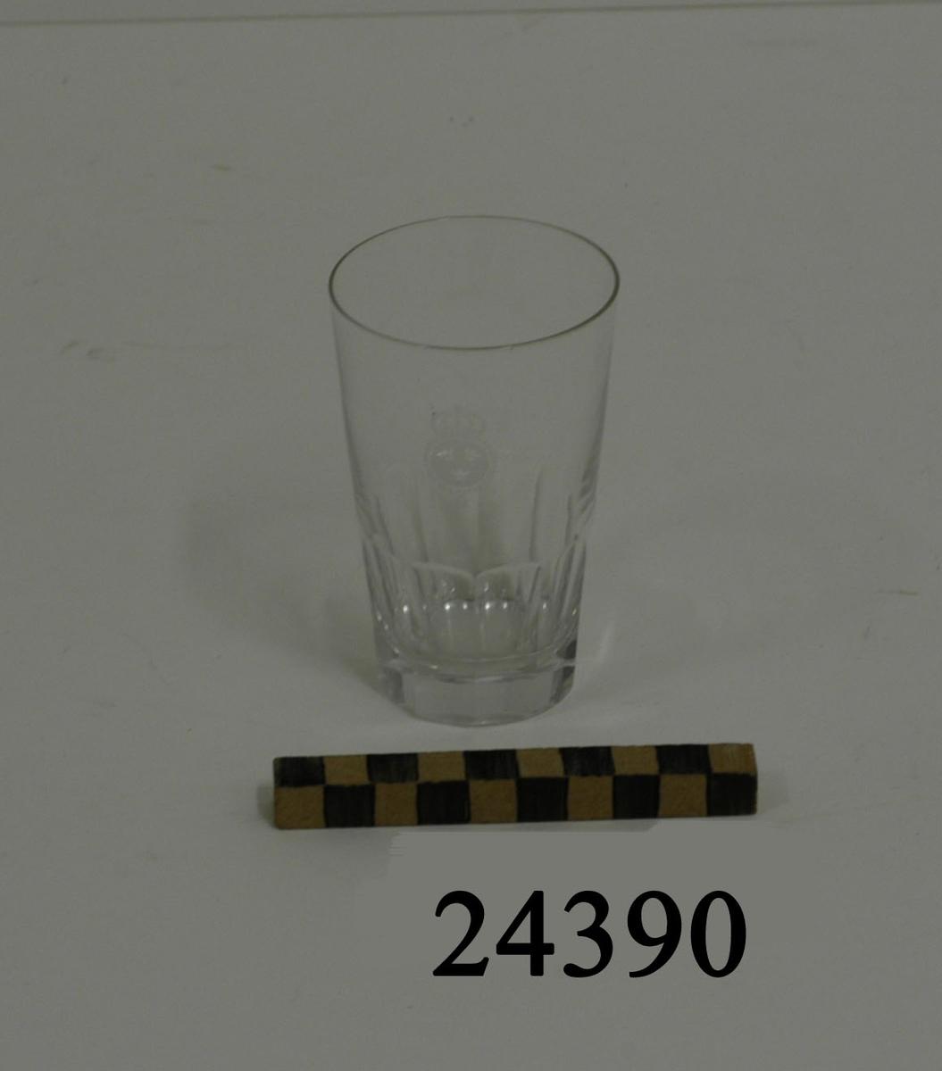 Selterglas, cylinderformat, tjock botten, utan fot, något större i mynningen än botten. Bågformad slipning i glasets nedre kant. På glasets mitt etsad dekor: lilla riksvapnet omgivet av koldinerorden. Diameter: 60 mm mynning,  D = 40 mm botten.