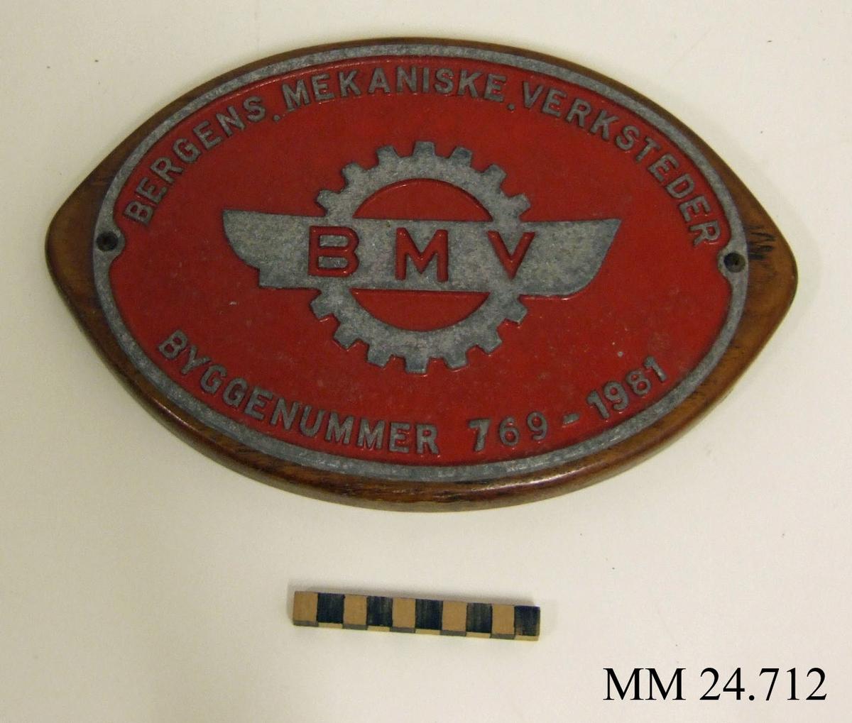 """Nybyggnadsskylt till patrullbåten Tordön. Oval, rödlackerad skylt av metall, med text i relief: """"Bergens Mekaniske Verksteder, Byggenummer 769-1981"""" samt logotype föreställande kugghjul och skeppsiluett. Skylten skruvad fast i ovalt, fenissat trästycke."""