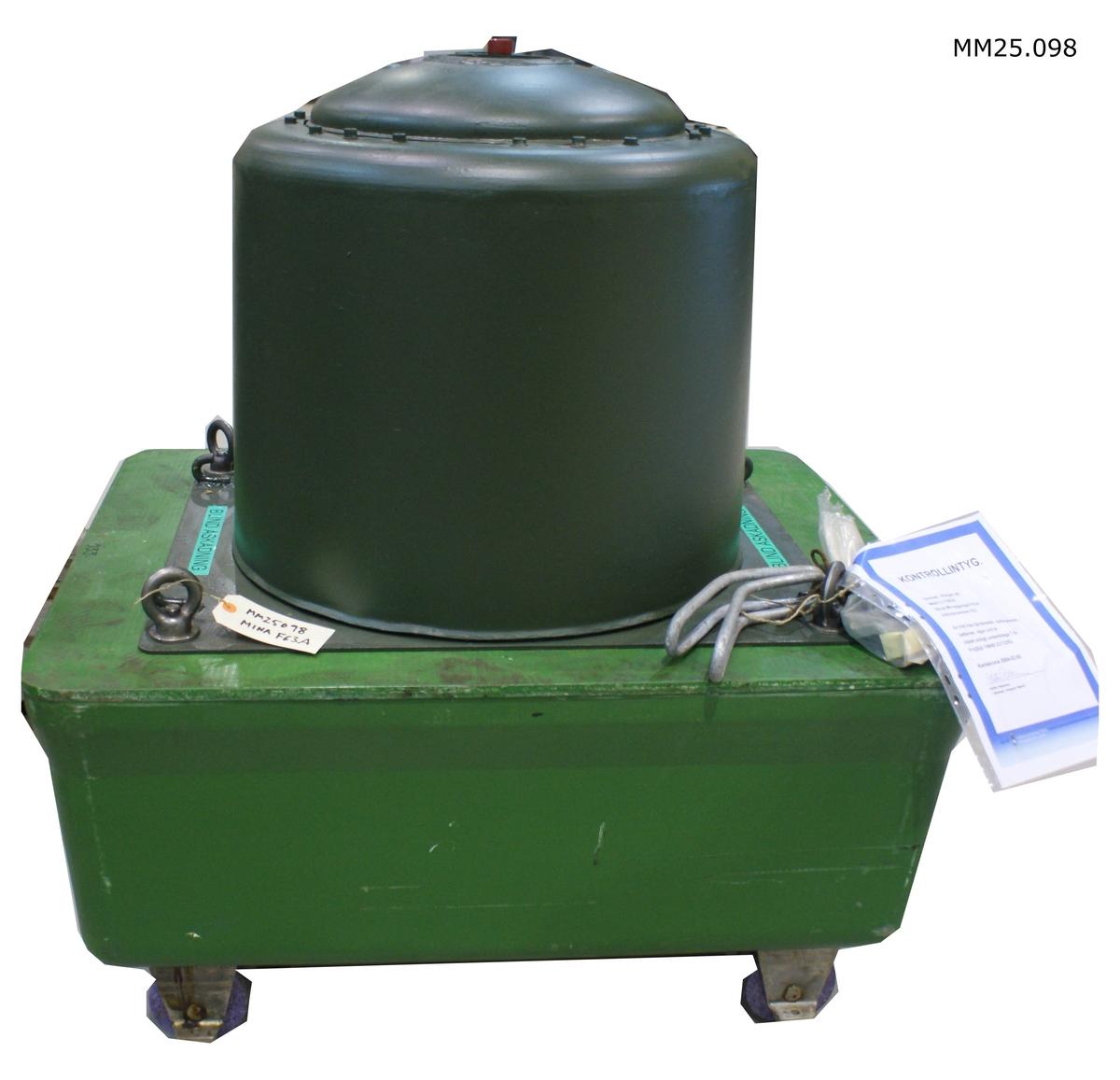 """Minan består av ett ankare som utgörs av en rektangulär liggande låda på vilket fyra rälsanpassade hjul sitter fästade. Ovanpå ankaret sitter minaggregatet vilket utgörs av en cylinder med en konkav rund del på. Hela minan grönmålad.  Minan har individnummer 033. Märkt """"Blind åskådning""""."""