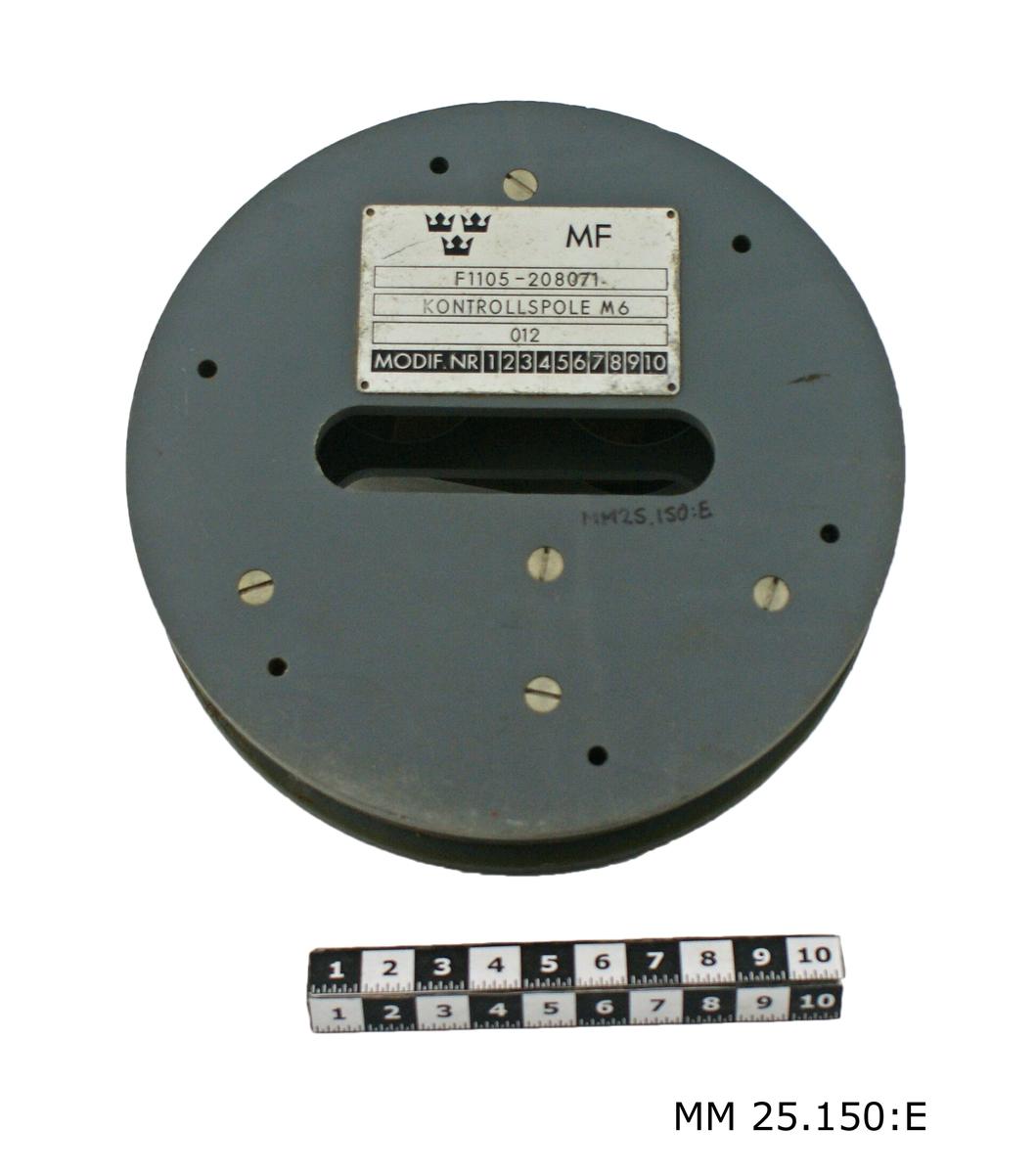 """Två runda sammanfogade baukelitdelar mellan vilka en spole ligger lindad pbakom skyddstejp. På ovansidan en vridbar styrklack. På undersidan en skylt i metall med tre kronor-stämpel och text: """"MF F1105-208071 KONTROLLSPOLE M6 012 MODIF.NR 12345678910""""."""