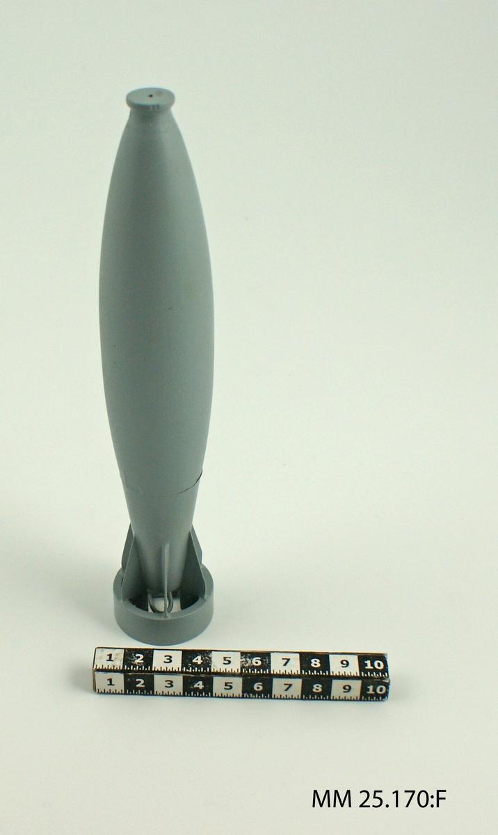 Grå raket med utdragen äggform. I botten av raketen sitter en dysa med sex vingar som löper från raketens kropp och ner i dysan. På undersidan syns slangar och rör. I toppen av raketen finns trattliknande form.