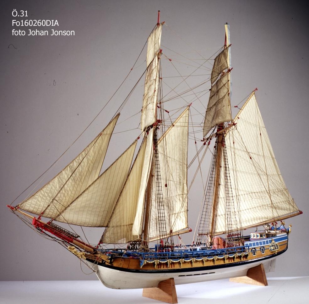 """Fartygsmodell, kunglig skonert, AMPHION. Riggad med segel och vimpel. Bordlagd på spant med däcksinredning. 16 par årtullar, 18 st åror. Rikt skulpterad, förgylld och blåmålad akterspegel med GIII:s krönta namnschiffer och två """"lilla riksvapnet"""", gallerier och brädgångar. Fernissad, med vit botten och svart berghult. Märsar, rundhultsnockar, bogspröt och block rödmålade. Galjon förgylld. 8 st nickor av metall. Tillverkad å flottans varv i Stockholm av daglönaren J. G. Carlström f 1829, d 1909, anställd å varvet 1858 - 1909, under åren 1902 - 1904. Segel, stående och löpande gods utfördes av riggaren å takelkammaren Ericsén och målningen utfördes å målarverkstaden. Skulpturerna utfördes av en träskulptör ej anställd på varvet. Amiral Hägg hade hela överinseendet."""