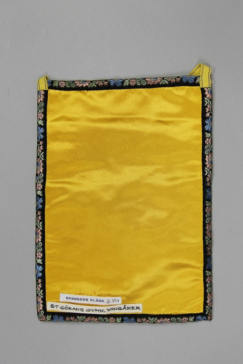 Kjolväska Fyrkantig modell med avskuret framstycke. Tillverkad av gul konstsidensatin med kedjesömsbroderi med konstsilkegarn i många färger Fickan fodratd med halvlinne. Kantat runtom med jacquardvävt blomband på svart botten  Bakstycke  av samma tyg. Midjeband av gul bomullmed rand i brunt.