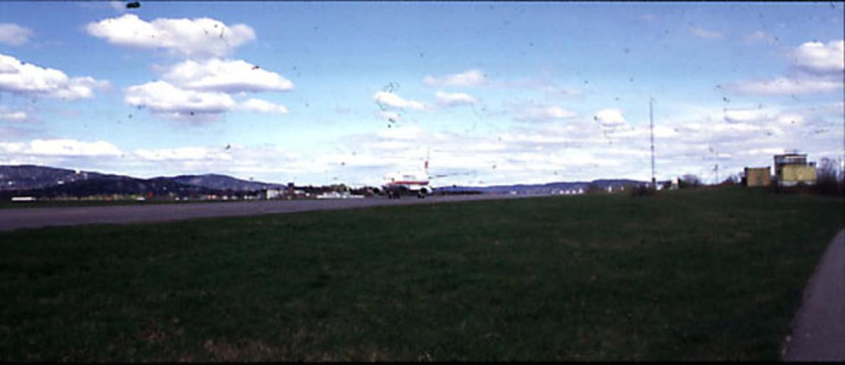"""Lufthavn, 1 fly på bakken, LN-BRR Boeing 737-500 """"Halvdan Svarte"""" fra Braathens Safe. Skrått forfra. Bygninger bak."""