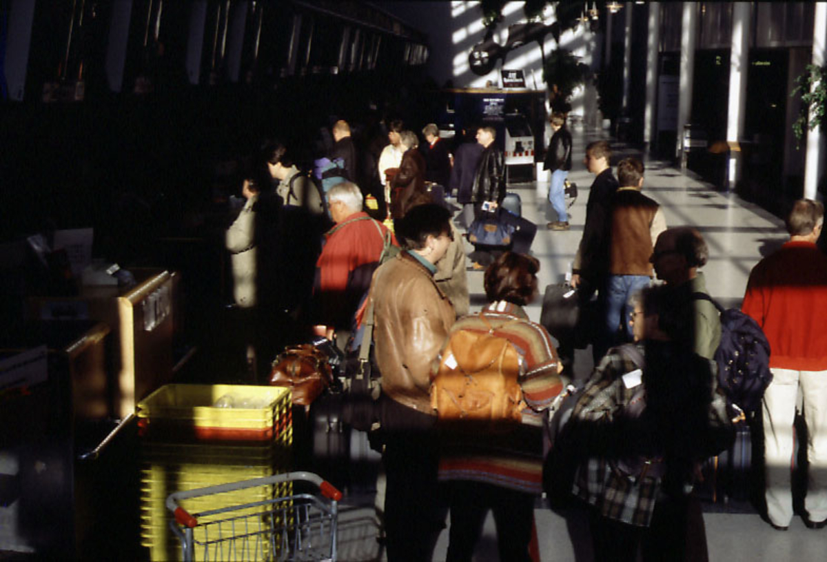 Lufthavn, flere personer med baggasje foran innsjekkingsskrankene i terminalbygningen.  1 automatisk innsjekkingsautomat i bakgrunnen.