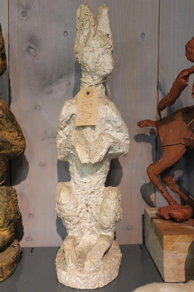 En skulptur i gips av en hare sittende på to. Se også nr. 102 og nr. 103.