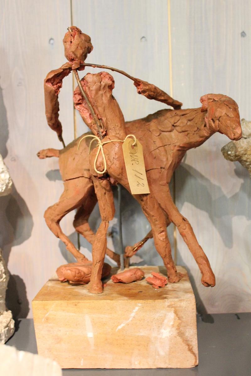 """Skulptur i leire av en hest og en gutt på sokkel i tre. Tittel: """"GUTT MED FOLE""""."""