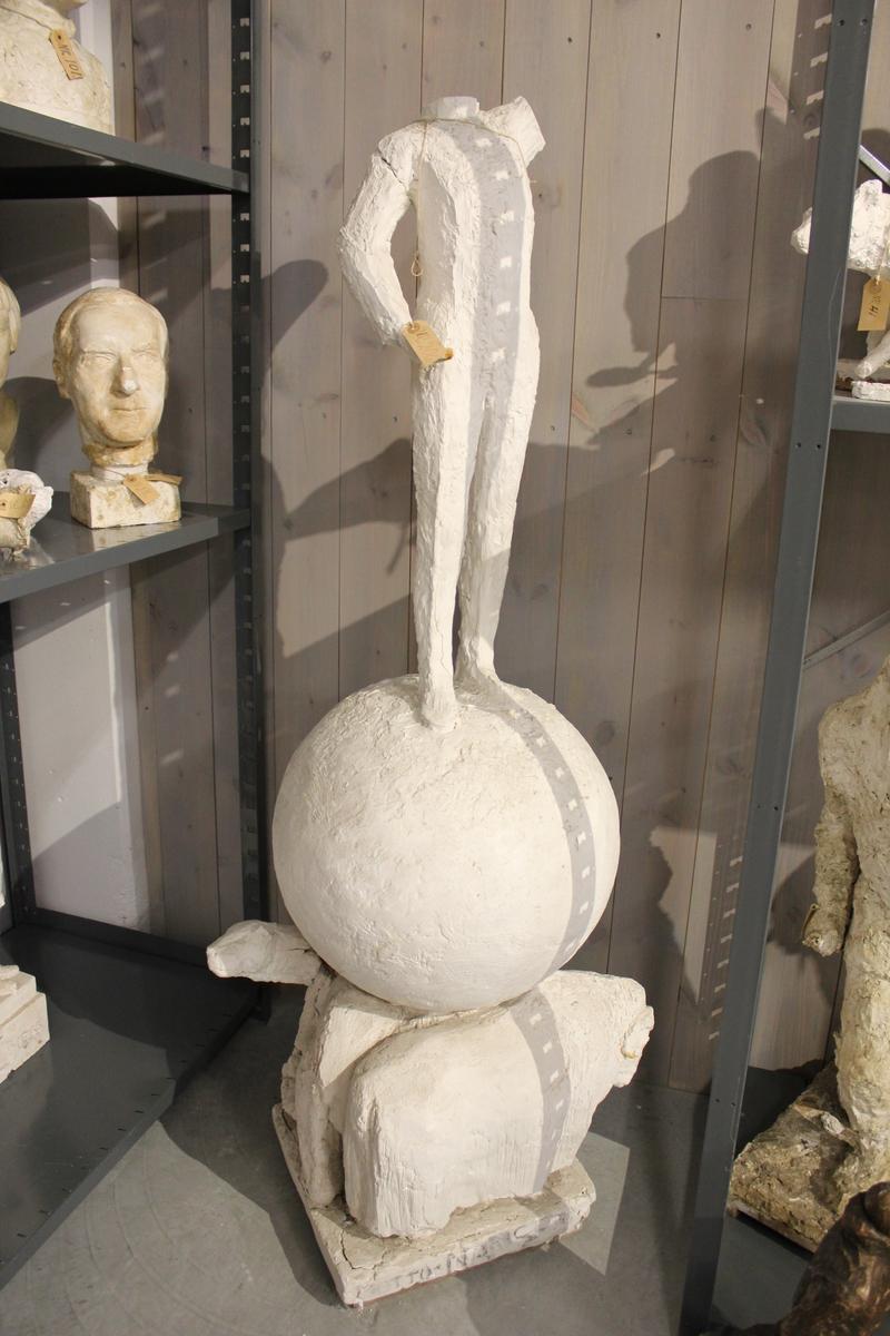 Skulptur i gips av Fritjof Nansen som står på en kule. Kulen ligger på ryggen til en moskus og to isbjørner. Han holder en arm ut med falk på. Dette er er et konkurranseutkast fra 1957. Armen har fått nr.207.
