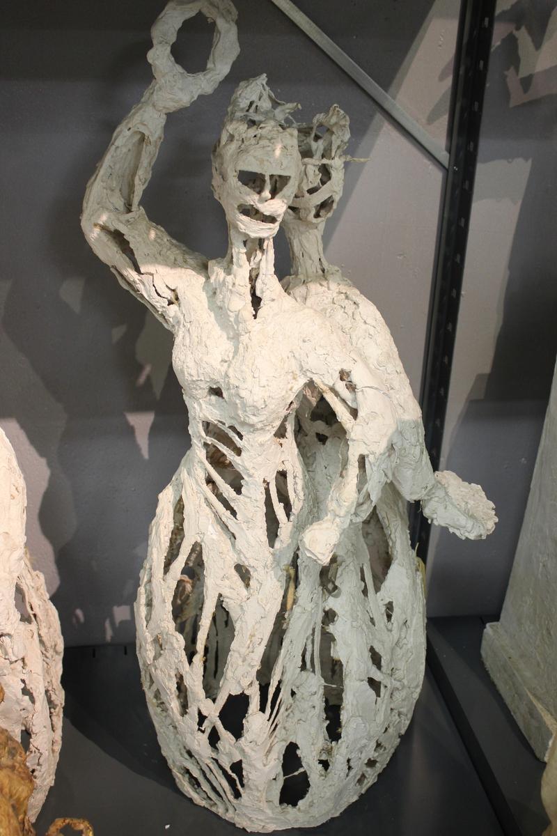 """Skulptur i gips av en kvinne med den ene armen over hode, med en ring i handa.. Utkast til """"Haldensøylen"""" 1/3 størrelse. Se også nr.021, nr.212 og nr.213. Haldensøylen ble laget til byens 300-års jubileum 1965."""