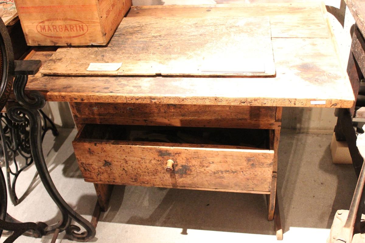 Står på to loddrette bord med list nede i hver ende. To skuffer, ei høyere enn den andre. Diskplate som går langt utover fotbord. Listekant rundt plate.