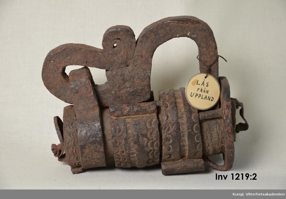 Lås, bultlås, utan nyckel. Låset är mycket kraftigt och försett med rika smidesutsmyckningar runt låshuset, med halvmånformade mönster inslagna i banden som omger låshuset. Enligt en vidhängande lapp är låset inköpt av kapten Ernst Malmberg, september 1934.  fr Wrå , Alsike, Uppland