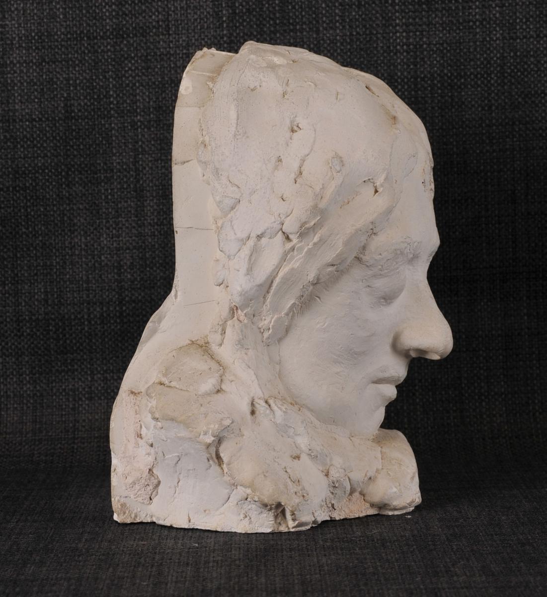Eit kvinneandlet, maske (?) som er hol inni. Augo er lukka og andletet er omkransa av hår.