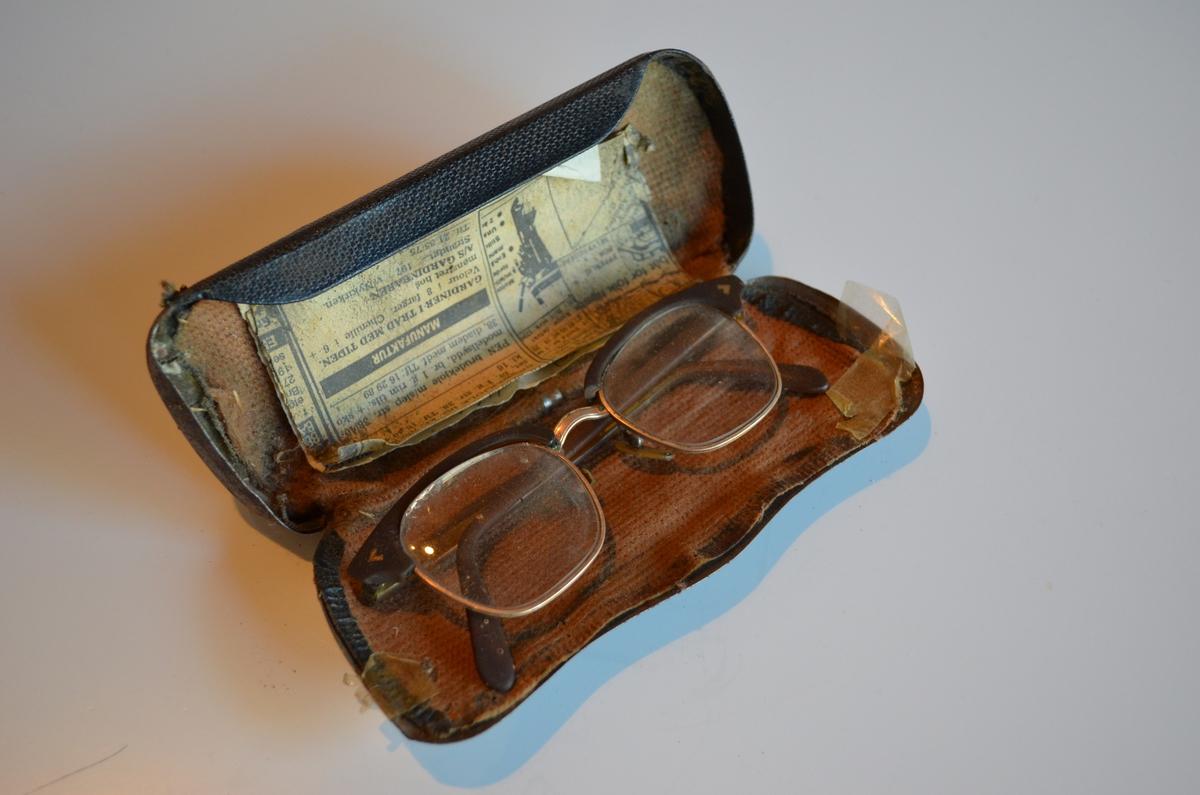 Brilleetui i metall. Belagt med stoff på insida. Stoffet er i ferd med å løsne og er festa med teip. Inni  etuiet ligg det eit avisutklipp og ein lapp med notater på. I etuiet ligg det også eit par briller: KSF.008492.