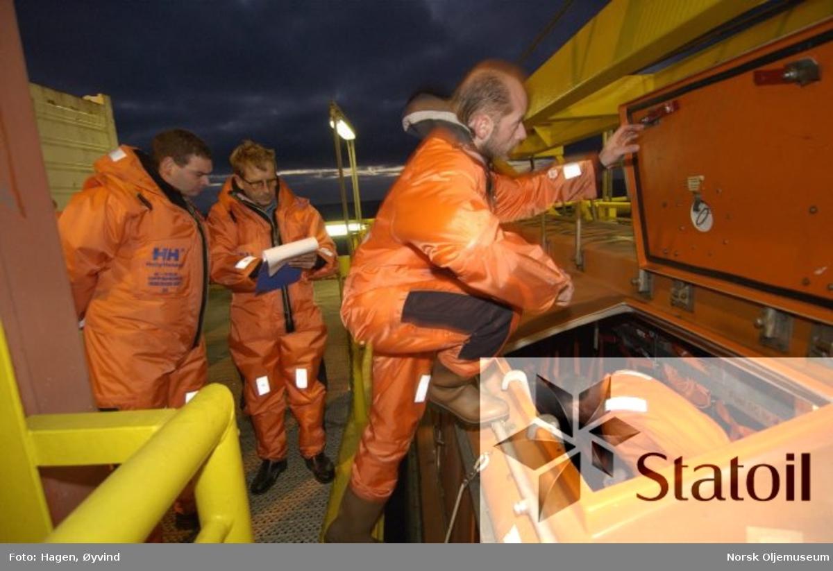 Livbåtøvelse på Statfjord C.  Ansvarlig person sjekker navn på personer som skal inn i livbåten.