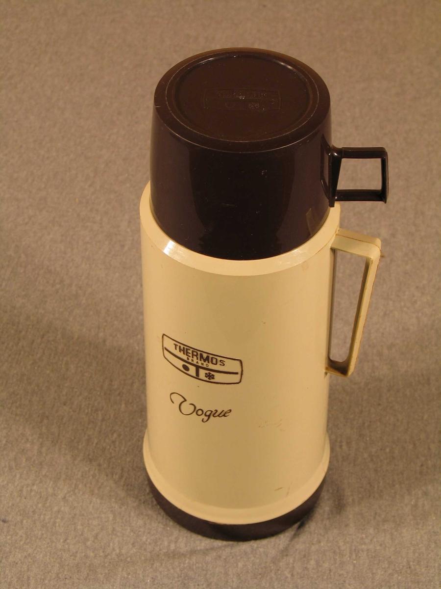 Fire deler: flaske, kork, 2 koppar..  Syllindrisk form med hank.Skrukork. Utanpå  er ein kopp utan hank og utanpå den igjen ein større kopp med hank. Glaskolbe inni.