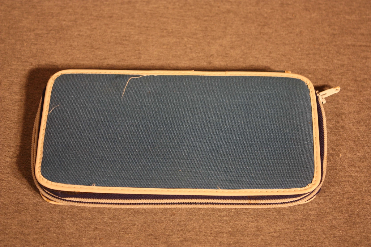 Penalhus med pappavstiving og trekt med tekstil. glidelås. Inni er strikk til feste av 16 blyantar. Utanpå er teikning av ein racerbil i gult og blått, nr. 131 (pålimt). Orange prislapp; kr 21,40