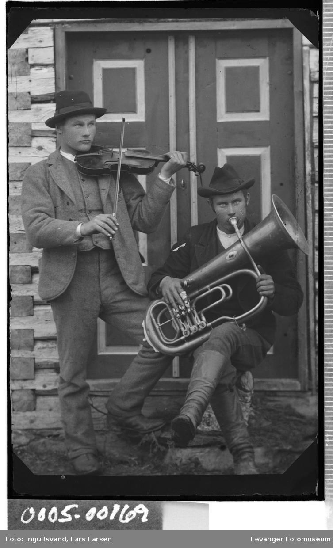 Portrett av to menn foran et inngangsparti, den ene spiller fiolin den andre horn.