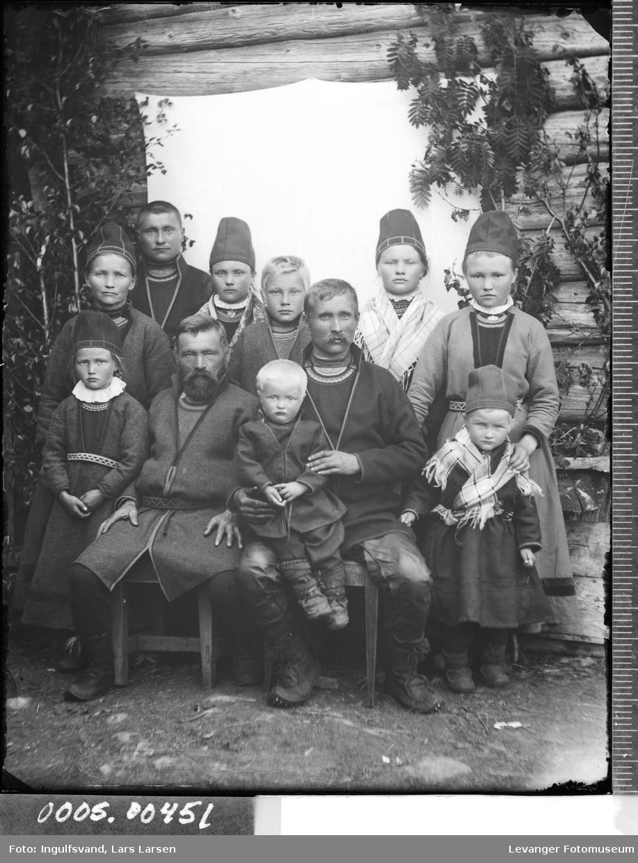 Gruppebilde av elleve mennesker i helfigur i ført samiske klær.