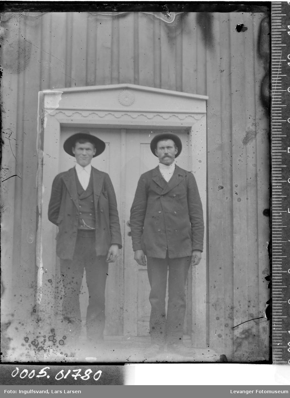 Portrett av to menn foran en dør.