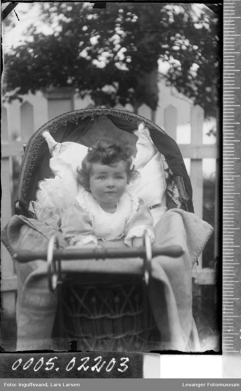 Portrett av en jente i en barnevogn.
