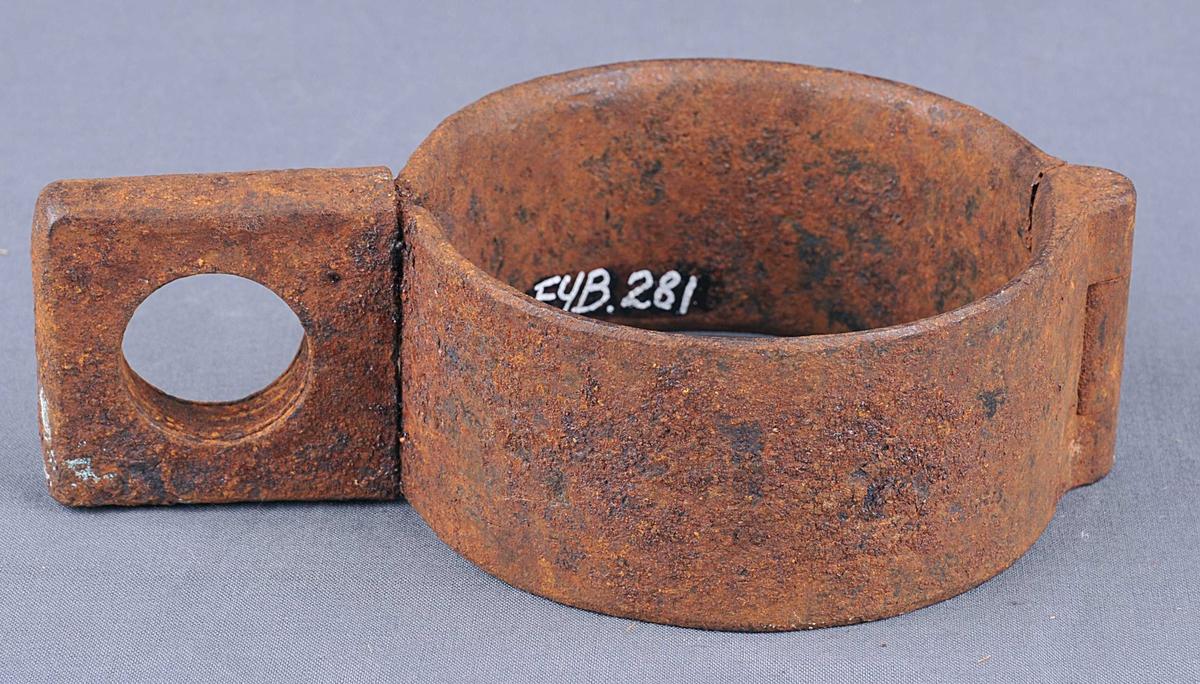 Sirkelforma fotjern. Hengsla i den eine enden, lås i den andre. Låsen er laga slik at endane på jernet er smidde ut i to plater som ligg flatt mot kvarandre. Hol gjennom.